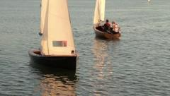 Two people in a dinghy sail in warm evening light Stock Footage