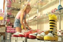 Stock Video Footage of Child Choosing Footwear in Shoe Store
