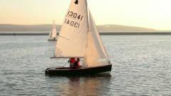 dinghy sailing in warm evening light, sail boat - stock footage
