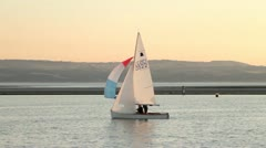 dinghy with spinnaker sails in warm evening light - stock footage