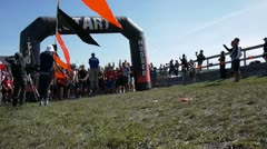 People crossing finish line of a mud race Stock Footage