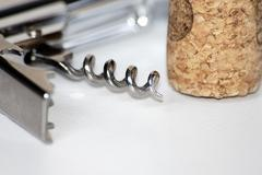 Vintage corkscrew with cork on a white background. - stock photo