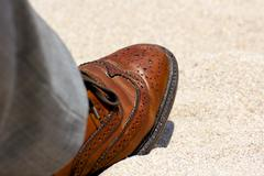 Close-Up of Men's Leather Shoe Worn on the Beach - stock photo