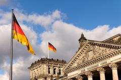 German Flags at the Reichstag Seat of the Federal Parliament in Berlin - stock photo