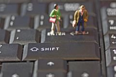 two figures on keyboard - stock photo
