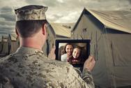 Stock Photo of Deployed Military Man Chats With Family on Computer