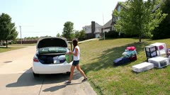 College age girl trying to pack car, but everything won't fit Stock Footage