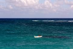 Tiny White Boat Alone on a Turquoise Ocean - stock photo