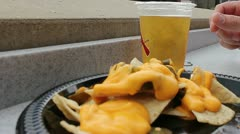 Close up of eating nachos and cheese with a beer Stock Footage
