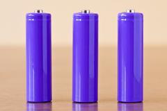 three purple alkaline batteries - stock photo