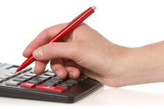 Calculator and hand with pen Stock Photos