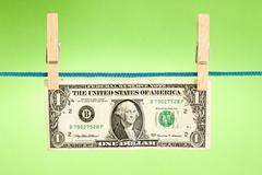 Stock Photo of dollar hung  over a green background