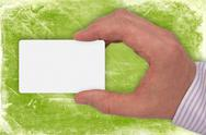 Stock Photo of hand with white card on green background