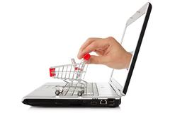 laptop and hand with shopping cart - stock photo