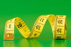 Stock Photo of measure tape on green background
