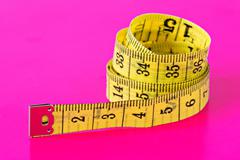 Stock Photo of measuring tape on vivid pink background