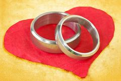 wedding rings on paper heart - stock photo