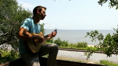 Man Plays Guitar Overlooking Train Tracks Stock Footage