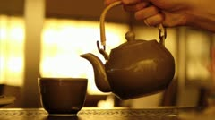 Hot water pouring from tea pot to tea cup Stock Footage