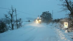 A snowplow mounted on a tractor in action at dawn on a rural road. Stock Footage