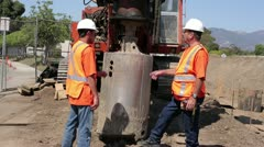 Construction workers discuss placement of heavy drill Stock Footage