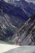 Climbers with full packs descending glacier Stock Photos