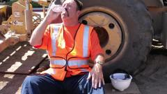 Construction worker drinks from plastic water bottle on hot day Stock Footage