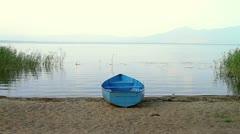 Small fishing boat on lake coastline Stock Footage