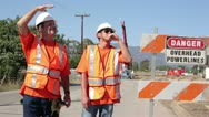 Construction workers discuss overhead power lines Stock Footage