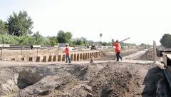 Construction workers crossing foot bridge over irrigation ditch Stock Footage