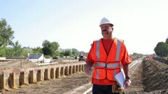 Construction worker surveying irrigation ditch on hot day Stock Footage