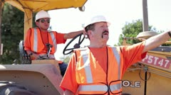 Construction workers surveying construction site on heavy machinery Stock Footage