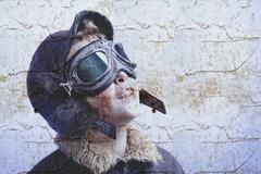 boy dressed up in pilot outfit. vintage style - stock photo