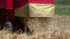 Combine releasing hay during wheat harvest Stock Footage