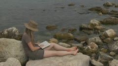Beautiful woman reading on the beach, book, learning, relax, coastline Stock Footage
