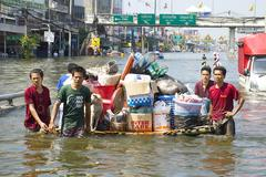 moving belongings on a raft during the 2011 thailand floods - stock photo