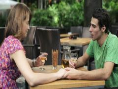 Couple drinking wine and holding hands in cafe, steadicam shot NTSC widescreen Stock Footage