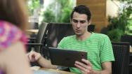 Stock Video Footage of Young couple with tablet computer in cafe, steadicam shot HD