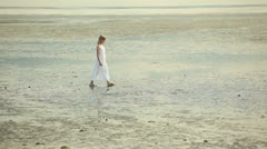 Young gril walking on a beach Stock Footage