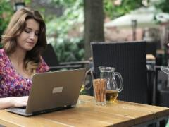 Happy couple with laptop drinking wing in cafe, steadicam shot NTSC - stock footage