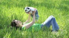 Mother sitting on the grass raising up her baby Stock Footage
