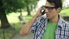 Young man talking on cellphone in the park, steadicam shot HD - stock footage