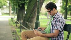 Young happy man with laptop in the park, steadicam shot HD Stock Footage
