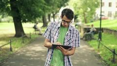 Young man with tablet computer in park, steadicam shot HD Stock Footage
