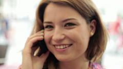 Beautiful woman talking on cellphone in the city, steadicam shot HD Stock Footage