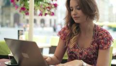 Young happy woman with laptop in the cafe, steadicam shot HD - stock footage