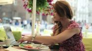 Stock Video Footage of Woman with laptop eating lunch in the cafe, steadicam shot HD