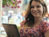 Stock Video Footage of Happy young woman with tablet computer in the city, steadicam shot NTSC