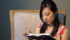 Young Asian woman sitting and reading a book - stock footage