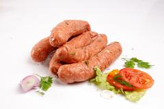 Sausages with fresh vegetables Stock Photos